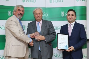 (L to R) Robin Amlot, the Managing Editor of Banker Middle East presents the award to Michael Tomalin, the Group Chief Executive of NBAD and   Fawaz Abusneineh, the Head of Debt Capital Markets at NBAD.